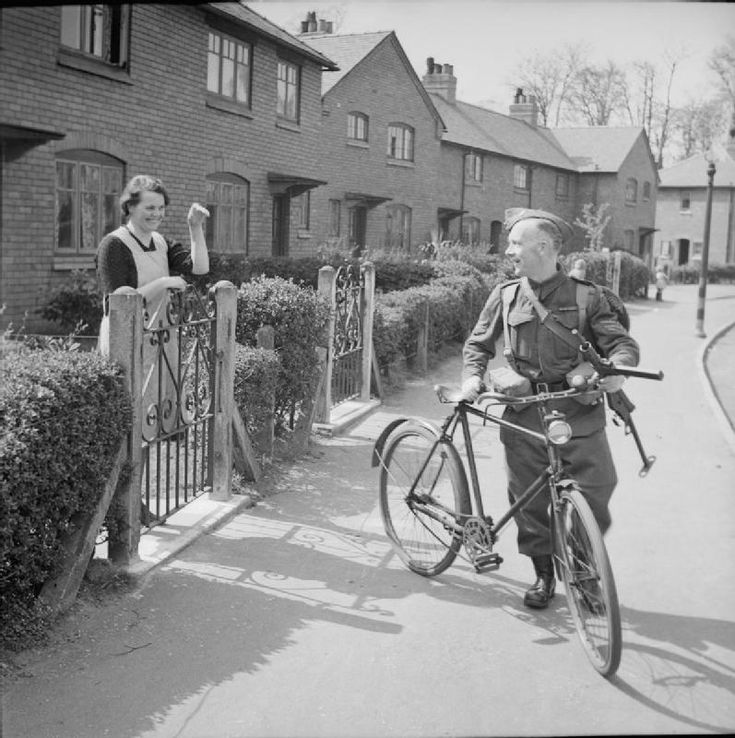 Sergeant Bill Davies, a colliery fireman from Gresford in North Wales, and the leader of a platoon of the colliery's Home Guard unit, bids goodbye to his wife as he leaves home to travel by bicycle to evening parade, 15 April 1943. Sgt Davies served in 13th Battalion the Royal Welch Fusiliers during the First World War.