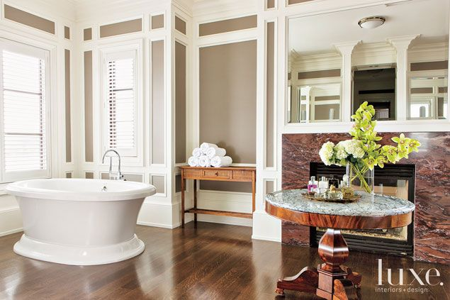 A two-tone paint job emphasizes the beauty of the architectural detailing in the master bathroom and complements the statuesque freestanding bathtub from Kohler. The sumptuous stone top of a vintage Edwardian table from Grant Antiques Gallery adds opulence to the setting.