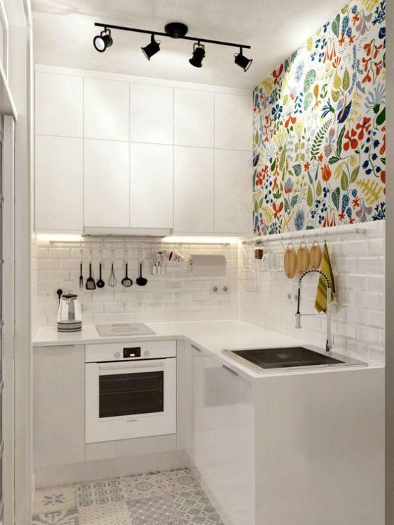 Małą kuchnię w całości zaaranżowano w bieli, urozmaicając jedynie jedną ścianę wzorzystym motywem. Gładkie fronty...