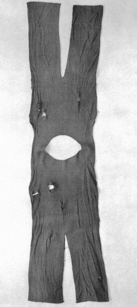 BOCKSTENSMANNENS KJORTEL treskaftad kypert. Den daterad till 1300-talet. Mått: hela kjortelstyckets längd 230 cm. Vidd nertill 250 cm. Halsringningens omkrets 82 cm. Ärmlängd höger 61 cm, vänster 59,5 cm. Ärmvidd nertill höger 23 cm, vänster 22 cm.