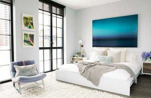 Camera con grandi finestre - Una bella camera da letto chiara con grandi finestre senza tende e un quadro oversize