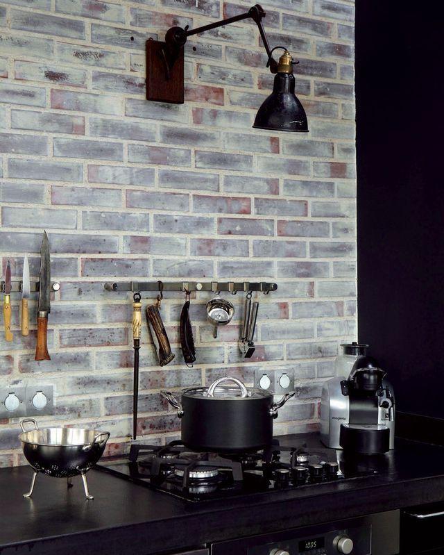 Briques véritables collées sur le mur (2 cm d'épaisseur, Briqueteries du Nord), patinées avec une lasure blanche.