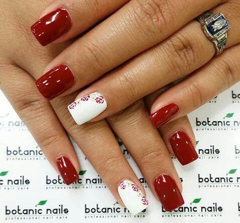 Uñas rojas con dos blancas y rosas rojas.