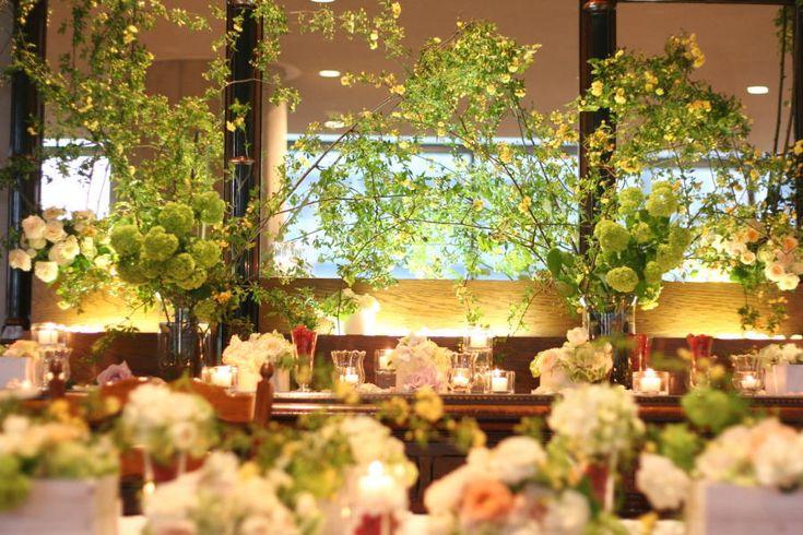 初台、新国立劇場にあるレストランマエストロ様の装花。メインテーブルの後ろに大きな鏡の台があって、そこにモッコウバラの小さな黄色が降り注ぐように、五線譜を描...