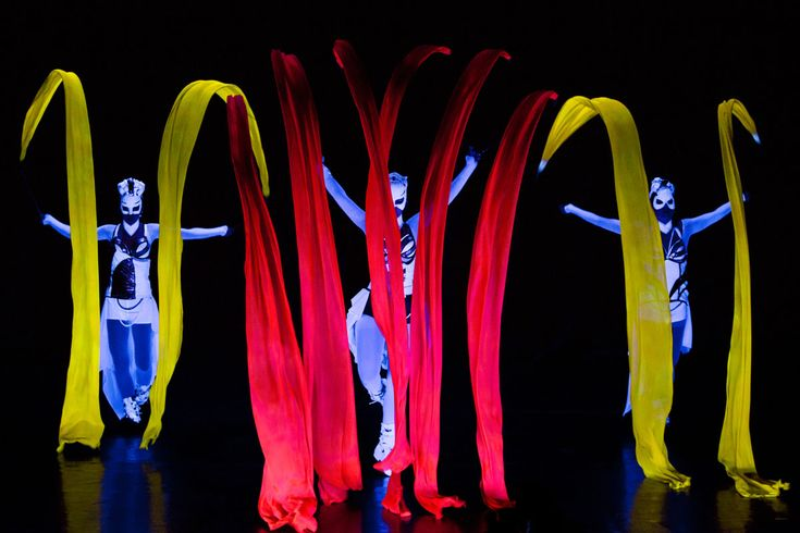 Red and yellow ribbons, dancers under black light in Crystal UV Light Show - Anta Agni. http://antaagni.com/crystal-light-show/