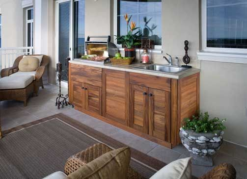 Small outdoor kitchen on a condo balcony. Louvered teak cabinets.