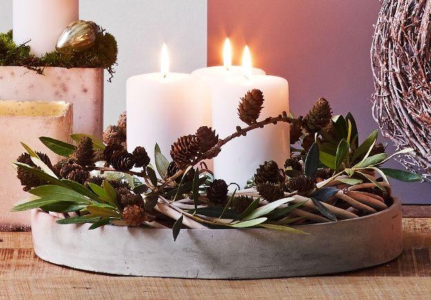 RUSTIK DEKORATION MED GRENE - Byg nemt din dekoration op med naturens grene og julekugler. Til denne dekoration er der brugt et cementfad og en natur krans fra Claus Dalby. Pynten er laurbær og lærkekogler. I midten omkring lysene er der lagt julekugler også fra Claus Dalby. #inspirationdk #inspiration #jul #advent #christmas #ClausDalby