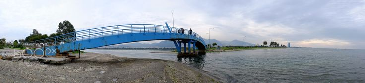 blue bridge - panoramic view of blue steel pedestrian bridge across the mouth of a fishing weir in balcova,izmir