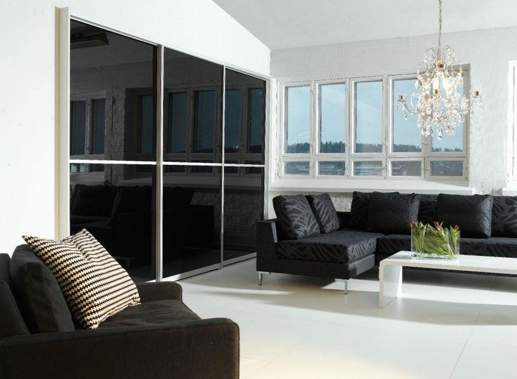 Rohkeaa kontrastia on luotu mustilla kiiltävillä liukuovilla sekä hohtavan valkeilla seinillä. #puuvaja