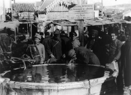 """Άνθρωποι και ζώα ξεδιψούν στην ίδια δημόσια ποτίστρα το 1918. Υπάρχει απαγορευτικό για τα ζώα του στρατού. Στο βάθος βλέπουμε ένα οπωροπωλείο με το όνομα """"ο Βενιζέλος"""" Φωτογραφία του Lewis Wickes Hine."""