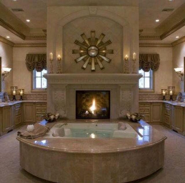 Jacuzzi in the middle of the bathroom with fire place ...