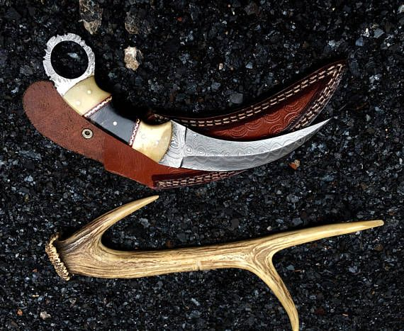 this is beautiful handmade damascus hunting karambit knife handle made of camel bone and buffalo horn comes with leather sheath ~ Total Length: 9 ~ Blade length:5 ~ Handle Length ; 4 ~ Blade Material: Damascus Steel 15N20 & 1095 Hand-Forged ~ Blade Hardness: 55-58HRC on Rockwell scale ~ Total Layers: 512 ~ Handle Material: Camel Bone buffalo horn ~Sheath: Genuine Cowhide Leather