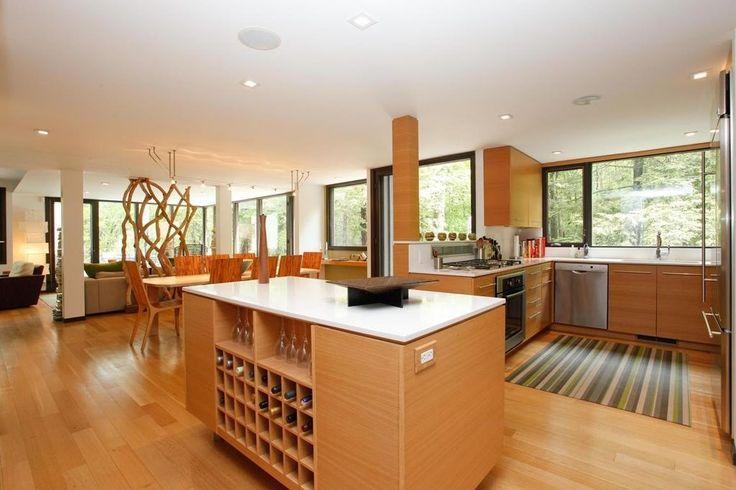 Polierten Furnier des Lichts getönten Holz Abdeckung der Kücheninsel in dieser Küche offenes Konzept, dass Funktionen dunkel gerahmten Glaswände.