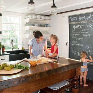 This restored Nantucket kitchen gets extra points for its fun and family-friendly chalkboard, where kids can draw and parents can record needed grocery items. The perfect-for-a-crowd island was constructed using salvaged wooden legs and a butcher block to