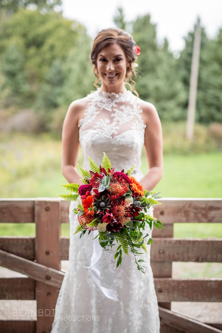 Hand held cascading fall bouquet. Pincushion, Celosia (brain flower), thistle, red Alstroemeria, Red Gerpoms, orange Gerbera's, Eucalyptus, Sword Fern and Italian Ruscus.  Picture by Beanbot Productions