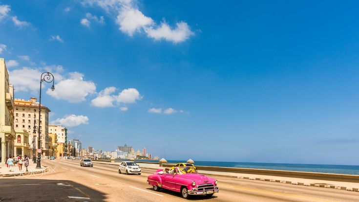 Retro car rides along the Malecon seafront in Havana - A red retro car rides along the road on the Malecon seafront in Havana. Vintage buildings, blue sky in white clouds and the ocean in the background