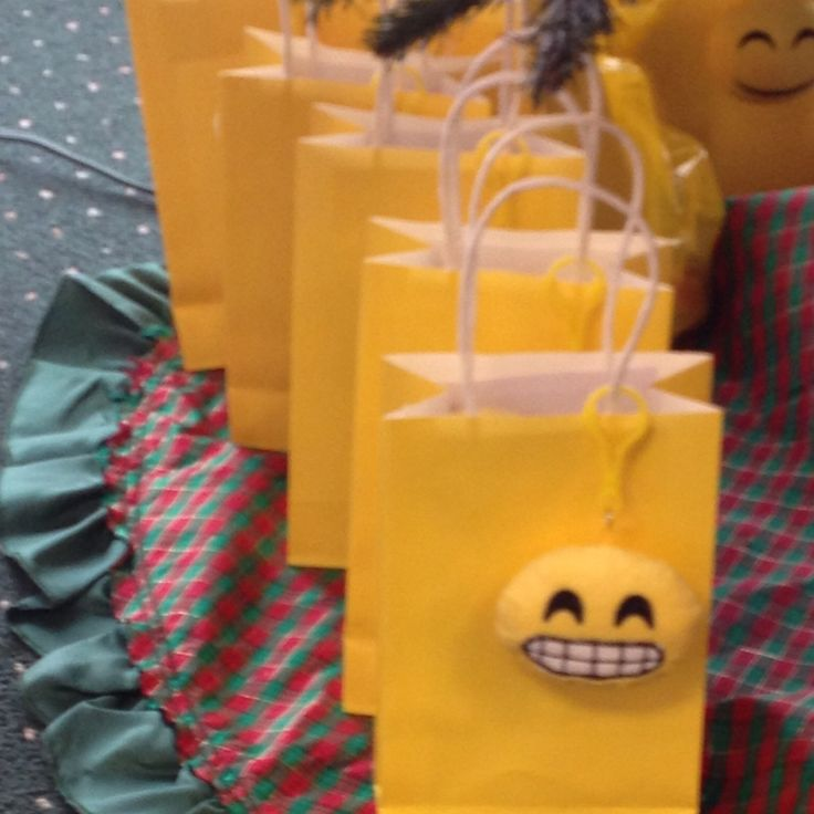 Emoji party favor bags (Dollar Tree) filled with emoji pens (Dollar Tree) and smiley note pads (Amazon), chocolate bar, and emoji key chain attached to bag (Dollar Tree)