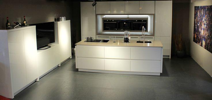 Strakke moderne hoogglans witte keuken met mat zwarte apparatuur.