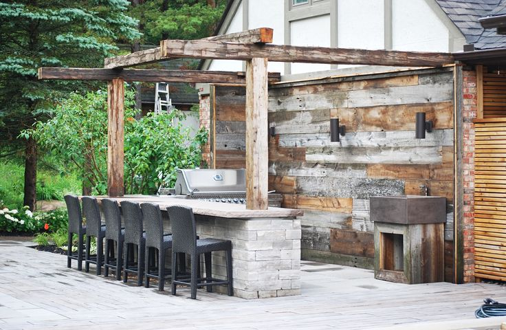 Reclaimed barn board feature wall and simple pergola paired with eramosa stone bar complete this outdoor kitchen