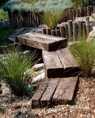 PETERSFIELD GARDEN WOODEN BRIDGE OVER SMALL STREAM. DESIGNER: MARK LAURENCE  clivenichols.com