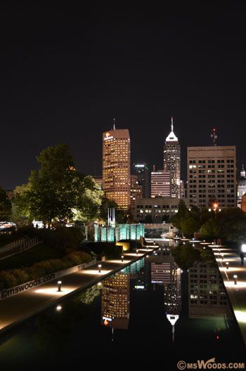 Photo of downtown Indianapolis skyline at night, with canal in foreground.