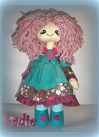 Sadie is a pretty little girl in green. She is wearing a cotton dress in green with a flowery trim and flowers on the top. Her shorts are check and on her feet, she has turquoise booties and socks. Sadie's hair is pink curly wool. http://www.marketdirect.ie/Dolly-Daydreamer-Doll-Sadie