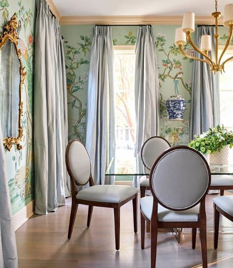 Amy Berry A stunning Chinoiserie dining room featuring many favorites - Chinoiserie wallpaper, silk curtains, a glass dining table, lucite, a gold mirror, and blue and white Chinese porcelain. Not a f