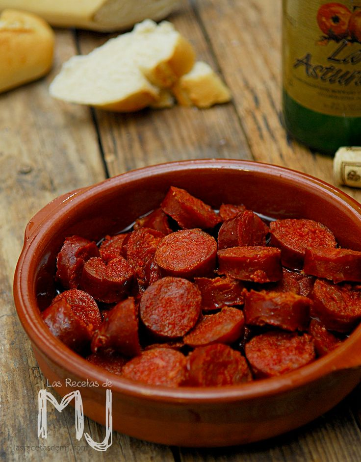 """Chorizos a la sidra. Spanish sausages """"chorizos"""" slowly cooked in cider. Dish from Asturias and Cantabria, very popular all over Spain."""