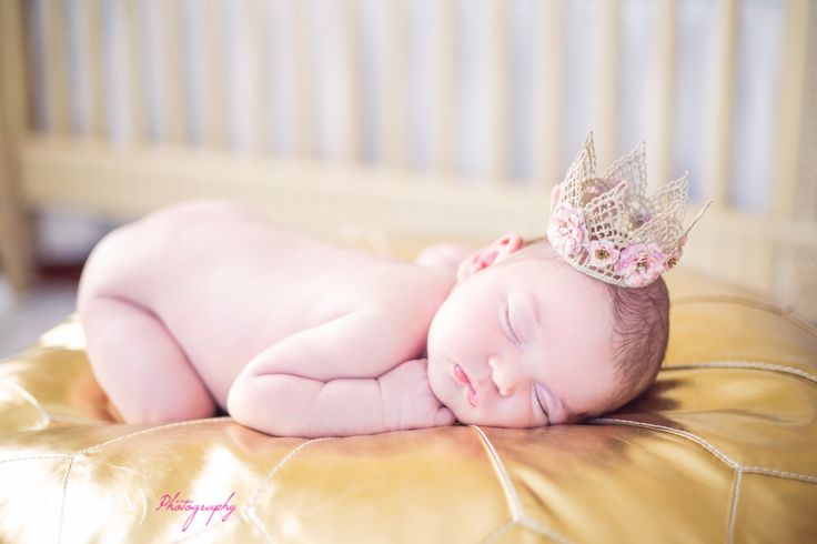 Newborn baby laying on a gold puff with bohemian handmade flower crown photographed by nj