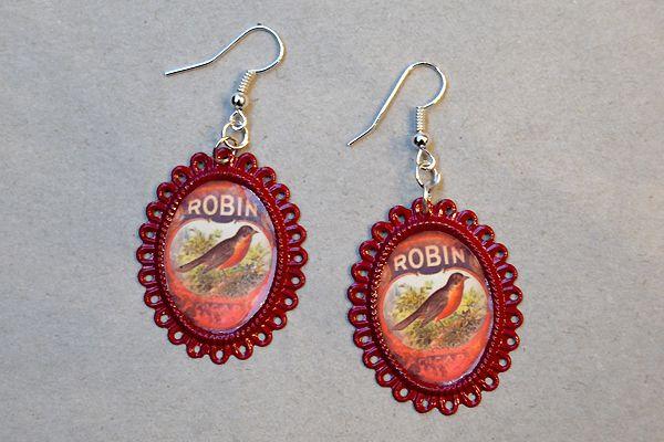 Earrings made of ornate oval-shaped frames and pictures of birds. http://www.minka.fi/korvakorut-kehyskorvakorut-c-36_104.html