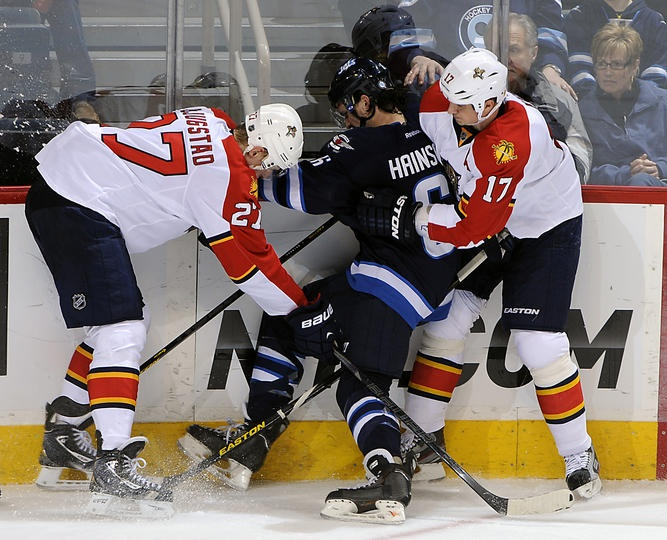 Florida Panthers at Winnipeg Jets Game W 7-2- 04/11/2013 Ron Hainsey #6 of Winnipeg gets sandwiched between Nick Bjugstad #27 and Filip Kuba #17 of Florida as they battle along the boards at MTS Centre.  (Photo by Lance Thomson/NHLI via Getty Images)