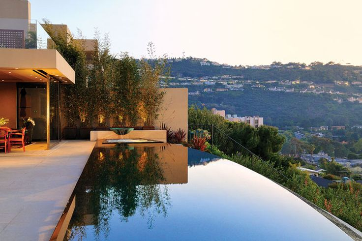 Built on a hill overlooking urban splendor, this infinity pool's clean lines and sweeping curve play a key role in a carefully planned design. Designed by Skip Phillips (of Questar Pools and Spas, Inc., Escondido, California) in conjunction with Island Architects and Bruce Rudd, Landscape Architect; Photography by Gary Conaughton http://www.luxurypools.com/builders-designers/questar-pools-and-spas-inc.aspx