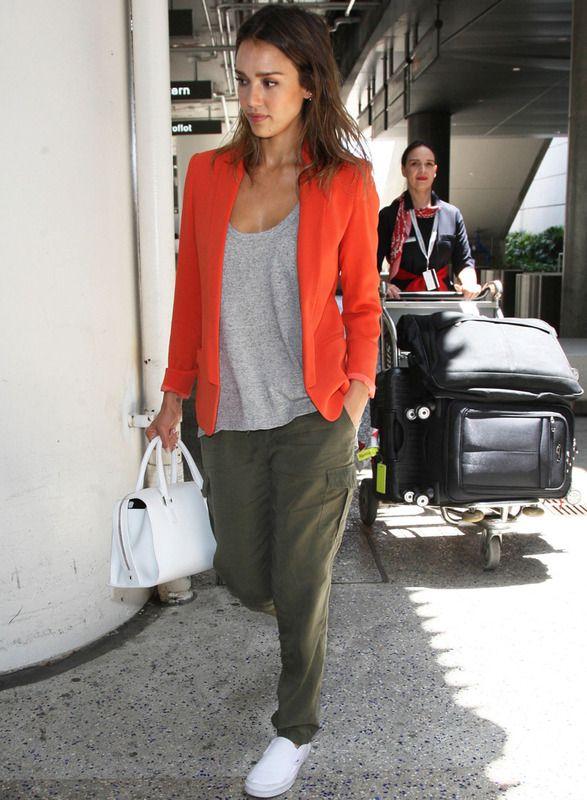 Jessica Alba: pantalones en verde oliva, camiseta básica gris, blazer naranja y complementos en blanco.