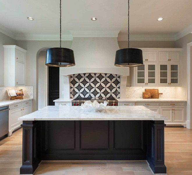Kitchen. Black and white kitchen features white cabinets adorned with brass hardware paired with white marble countertops and backsplash. A white kitchen hood with corbels stands over a black and white circle tile backsplash, Cement Tile Shop Circle Tile, and a Wolf range. A pair of black drum pendants, Arteriors Anderson Iron Pendants, illuminates a black kitchen island topped with contrasting white marble. Elizabeth Garrett Interiors