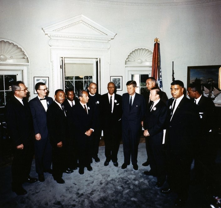 1963. 28 Août. ST-C277-1-63. By Cecil W. Stoughton. President Kennedy meets with the leaders of the March On Washington in the Oval Office. At the meeting were (from left to right) Labor Secretary Willard Wirtz, Mathew Ahmann, Rev. Martin Luther King Jr., John Lewis, Rabbi Joachim Prinz, Rev. Eugene Carson Blake, A. Philip Randolph, President Kennedy, Vice President Lyndon Johnson, Walter Ruether, Whitney Young, Floyd McKissick. Cecil Stoughton