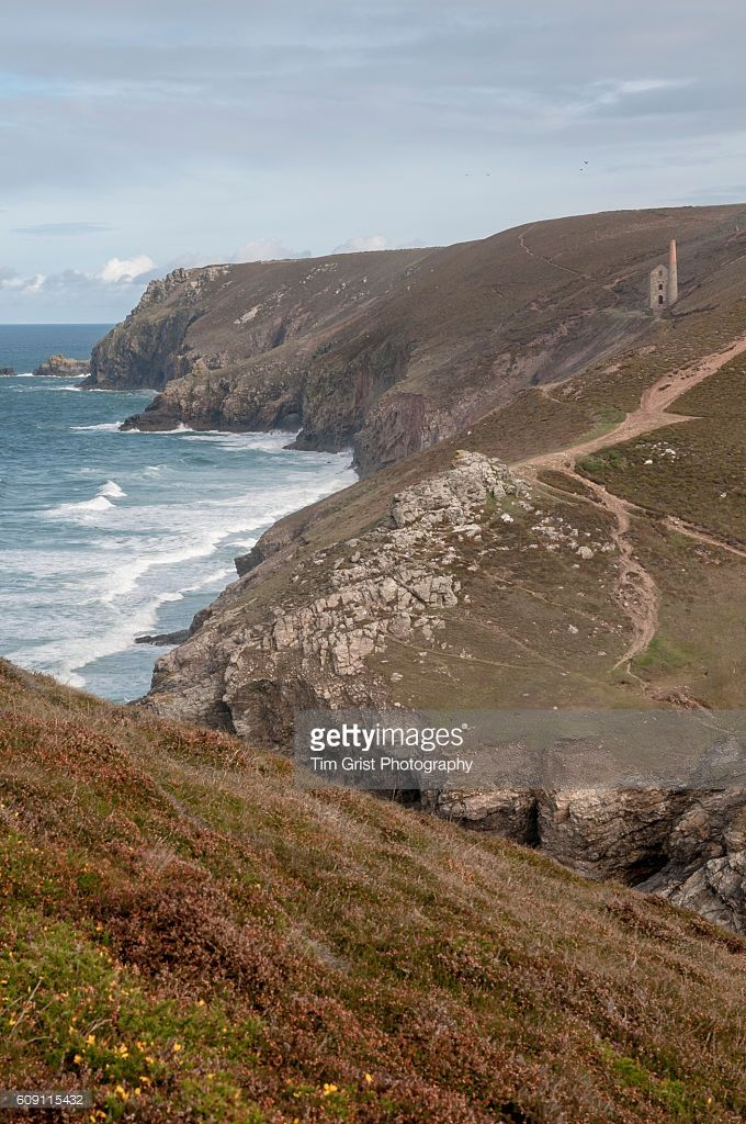 The coast near Chapel Porth, Cornwall with the ruins of the Wheal Coates Tin mine on the cliffs in the distance.