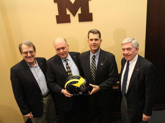 University of Michigan former coach Lloyd Carr, Athletic Director Jim Hackett, head football coach Jim Harbaugh, and former coach Gary Moeller pictured together wearing block 'M' lapel pins by Beliza Design.