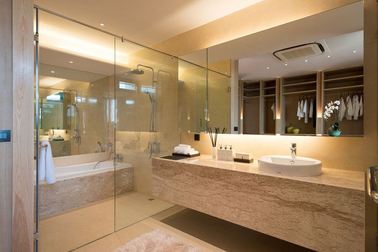In this master bathroom, a large bath/shower room is enclosed behind a glass wall, and a large back lit mirror makes the bathroom feel even larger.