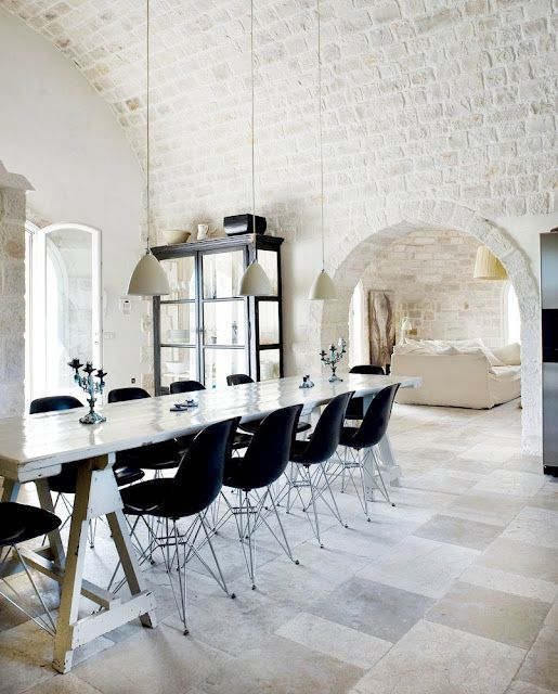 Exposed limestone brick wall, dining room with long farmhouse trestle table, black Eames chairs and pendant lights! http://cococozy.com