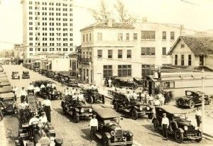 The square building at the center of this photo is the old Palm Beach Post-Times building in 1926. The view is from Dixie Highway looking east down Datura Street. The Harvey Building, still under construction, is in the background, and the West Palm Beach Fire Department and their equipment are in the foreground. (Courtesy of the Historical Society of Palm Beach County)