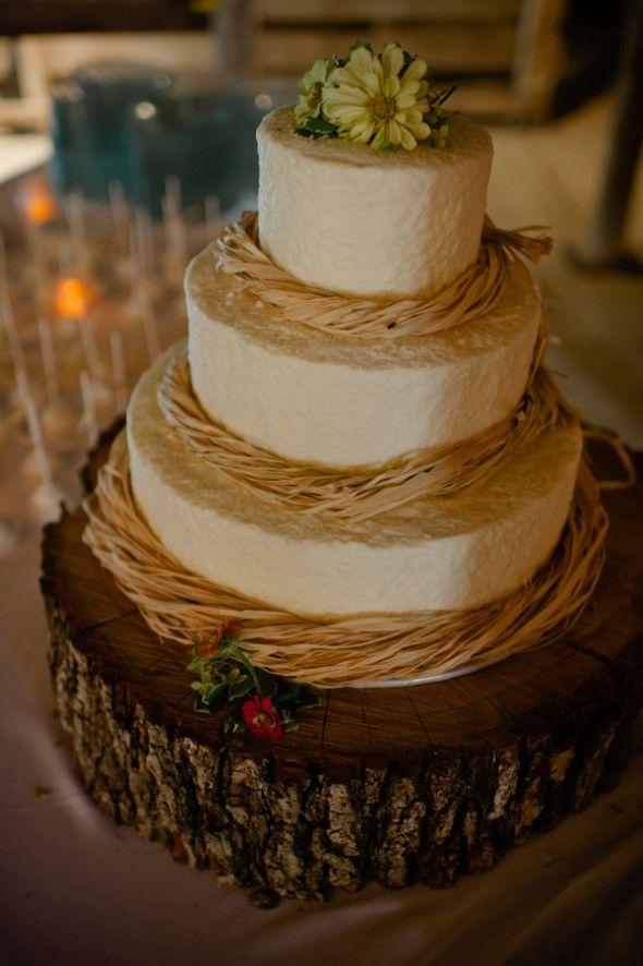 Rustic wedding idea: Tree slab as cake base and raffia decorations on wedding cake   Nebraska Barn Wedding: Ashley Tyler