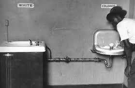La photo représente la ségrégation raciale, caractérisée dans les années 1930 aux États-Unis. Il est question d'une séparation physique des personnes de couleurs différentes dans les activités de la vie quotidienne et institutions publiques. Elle commença officiellement aux États-Unis avec l'arrêt Plessy v. Ferguson de 1896, pour la séparation des Blancs et des Noirs, dans les transports publics, en plus de la doctrine « Separate but equal » qui légitime la législation ségrégationniste du…