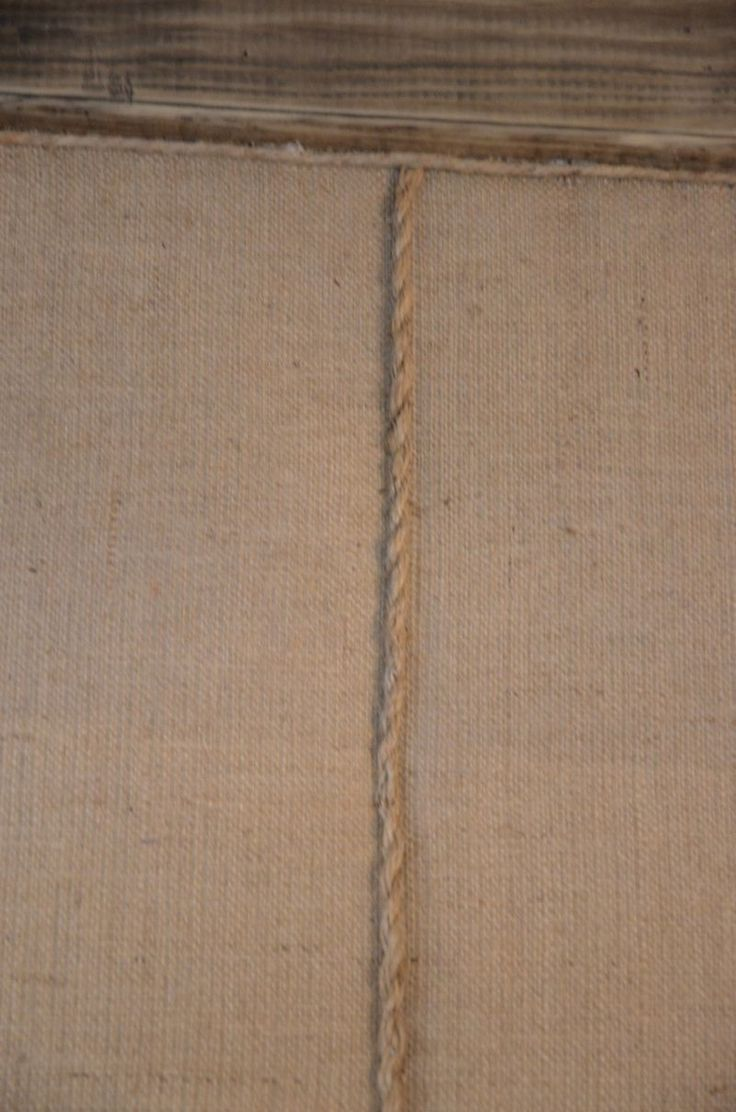 Great for a laundry/mud room. Rope trim on burlap upholstered wall