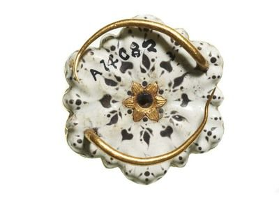 Brooch: An enamelled gold brooch in the form of a sexfoil rosette. The bezel comprises six briolette amethysts with a small diamond in the centre and six more around the edge to represent the calyx points of a rose. The reverse is enamelled in black and white. Also on the back are two opposing and recurving wires for attachment. Part of the Cheapside Hoard. Production Date: early 17th century ID no: A14082 Materials: gold; amethyst; diamond; enamel Status: permanent collection