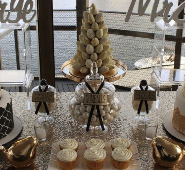 White and gold event styling at Berth . The dessert table features white chocolate strawberry  tower, cup cakes and themed party sweets.