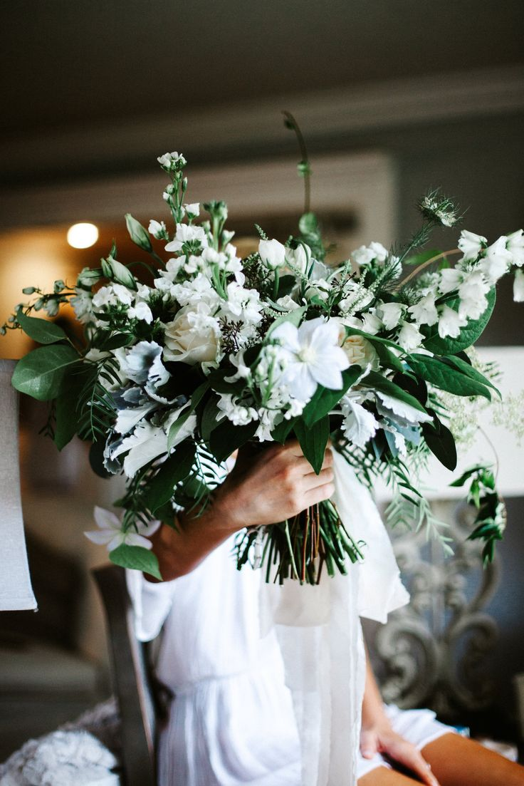 just delivered loose and organic hand tied bridal bouquet of white clematis,white and ivory roses, white delphinium, white larkspur, white stock, white nigella, white lisianthus, lemon leaf, dusty miller, seeded eucalyptus, jasmine vine and fern.
