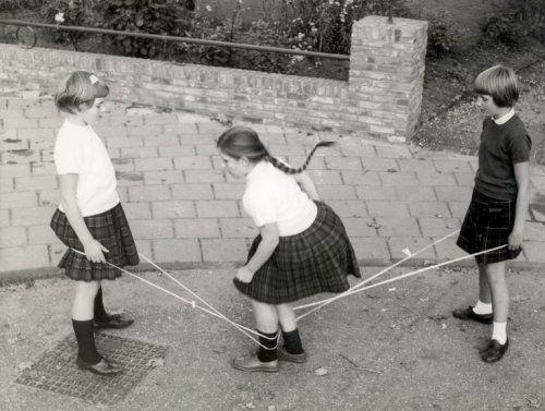 Onbekend | Drie meisjes spelen elastiektwist. In het midden is één van hen met haar benen verstrikt in het elastiek. Nederland, datum onbekend.