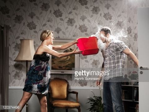 Stock Photo : woman thowing a bucket of water at her partner