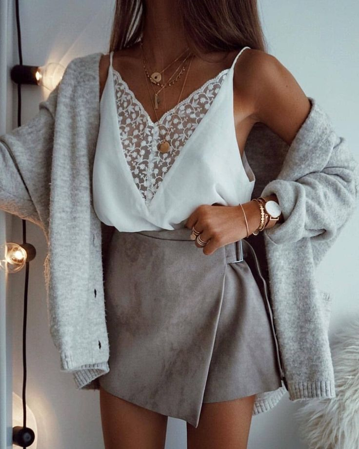 Gray cardigan over white lace cami and gray suede mini skirt.