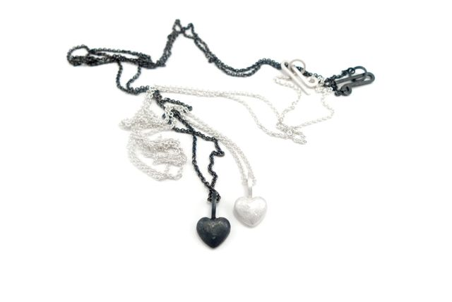 Silver hearts in chains. Black oxidized and white unpolished. By Karina Bach-Lauritsen.